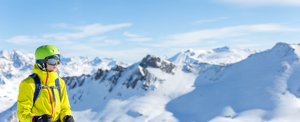 Panoramic image of man in helmet and with snowboard against background of snowy landscape