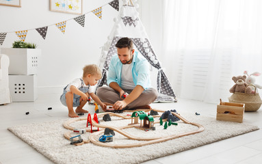 happy family father and child son playing   in toy railway in playroom