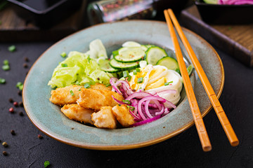 Salad from eggs, fried fish and fresh vegetables. Asian cuisine.