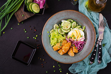 Salad from eggs, fried fish and fresh vegetables. Asian cuisine. Top view