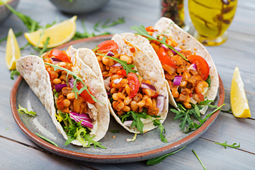 Mexican tacos with beef, beans in tomato sauce and salsa