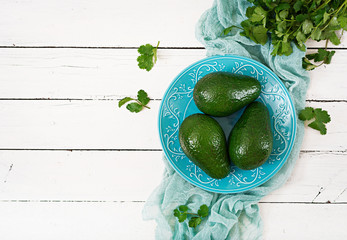 Three ripe avocados on a wooden table. Healthy food concept. Top view