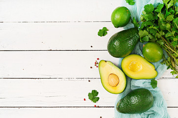 Ripe avocado, lime and cilantro on a light wooden table. Healthy food concept. Top view