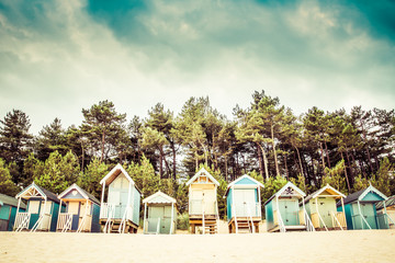 A row of beach huts on the sandy beach of Wells Next The Sea in Norfolk, UK with a tree line and summer sky.