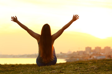 Cheerful woman raising arms at sunset