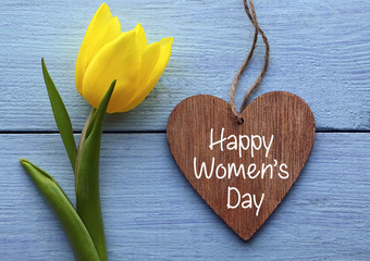 Happy Women's Day.Yellow tulip and decorative wooden heart on blue wooden background.International Women's Day greeting card.Selective focus.