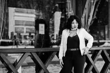 Stylish african american plus size model against wooden cafe at winter day.