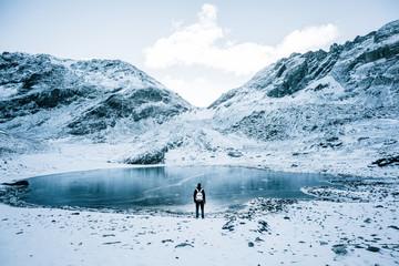 Tourist at lake in winter