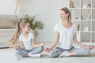 happy mother and daughter sitting in lotus pose at home together