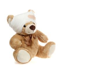 Teddybär mit verbundenem Kopf sitzt vor weißem Hintergrund