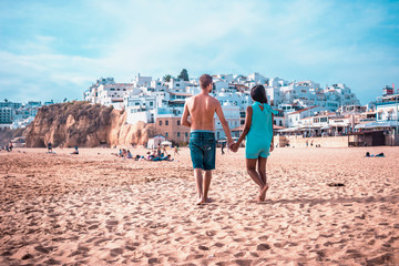 Happy young couple walking on the beach of Albufeira Algarve Portugal