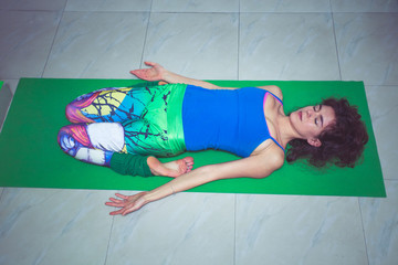young woman practice yoga lying in reclining hero position indoor shot
