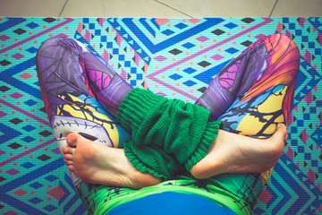 woman legs in colorful leggings in lotus pose from above view indoor