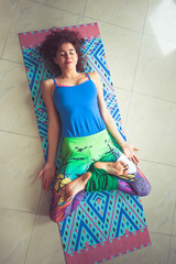young woman lying on mat with legs in lotus position indoor shot from above