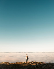 Man standing at cliff over clouds