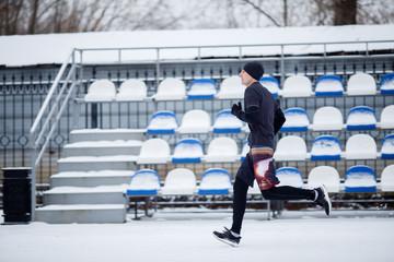 Photo of running sportsman in stadium at winter