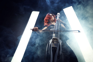 The cellist girl performs on stage.