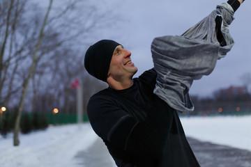 Image of man dressing sweater at stadium on winter