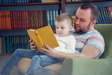 Photo of dad reading to son book sitting in chair