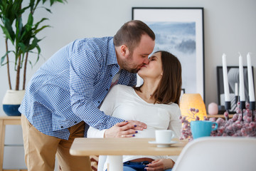 Photo of happy husband kissing pregnant wife