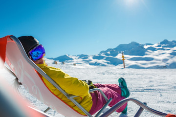 Photo of sporty woman in helmet sitting at snowy resort