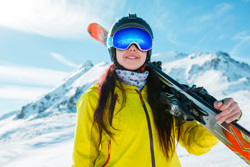 Picture of girl in helmet, mask with skis on her shoulder