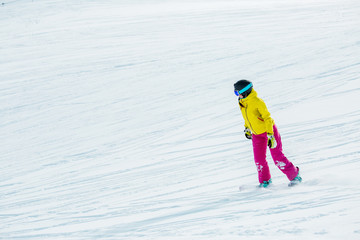 Image of athlete girl wearing helmet in sports clothes snowboarding