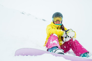 Photo of sporty woman wearing helmet and mask with snowboard sitting on slope of snowy hill
