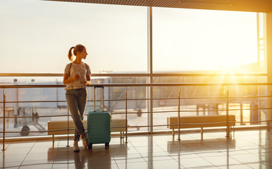 young woman waiting for flying at airport at window with suitcase  .