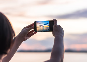 Smartphone camera in tourist woman person's hands who taking photo on touch screen of beautiful seascape sky with clouds during sunset at golden happy hour at dawn