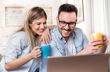 Young couple looking at laptop at home