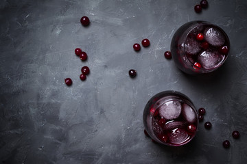 Alcohol cocktail with cranberries and ice, gray stone background, top view