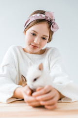 selective focus of smiling girl holding cute furry rabbits on white