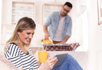 Man ironing while woman resting