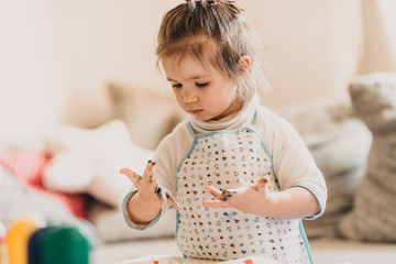 toddler girl in drawing apron draws fingers at home