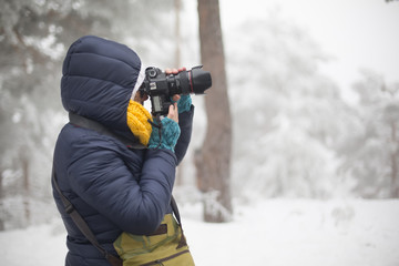 woman with camera in snowy mountains