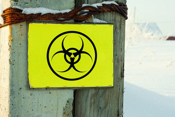 Biohazard danger outdoor sign. Rough lamppost with yellow beware old plate.