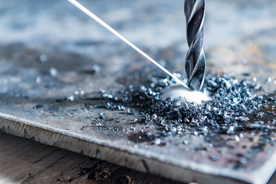 close up of drilling a hole with metal shavings an beam of lubricate liquid