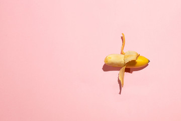 Sweet juicy opened small banana on pink table. Sexual life libido, penis size and potency concept
