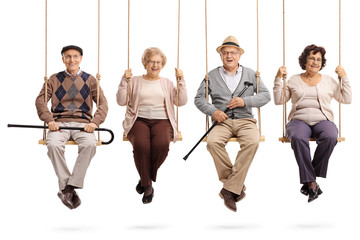 Cheerful seniors sitting on wooden swings and looking at the camera