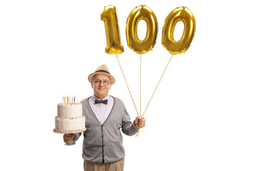 Mature man holding a birthday cake and golden number hundred balloon