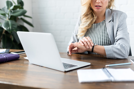 cropped image of businesswoman looking at watch on office with laptop