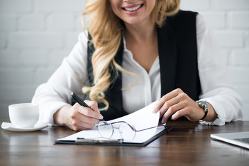 cropped image of businesswoman writing something to clipboard at office