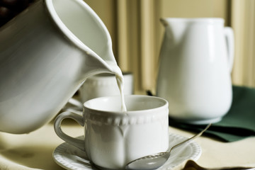 serving milk in a white ceramic cup