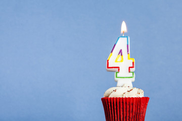 Number 4 birthday candle in a cupcake against a blue background