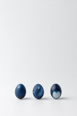 three blue painted easter eggs on white