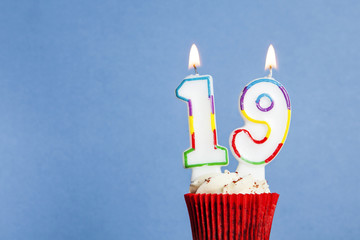 Number 19 birthday candle in a cupcake against a blue background