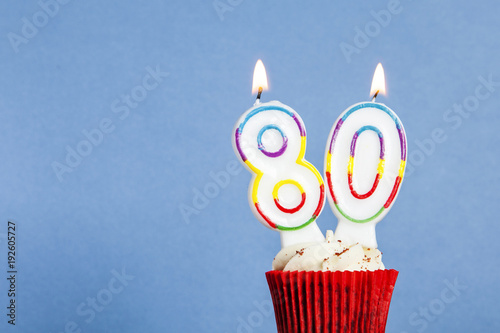 Number 80 Birthday Candle In A Cupcake Against Blue Background