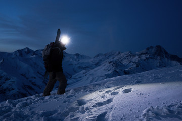 Professional tourist commit climb on great snowy mountain at night. Wearing backpack, headlamp and ski wear. Backcountry. Brave extreme traveler with a snowboard behind his back climbs winter slope Wall mural