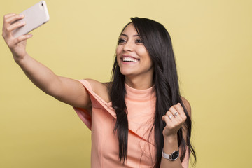 Portrait of a young cute brunette woman making selfie photo on smartphone isolated on a yellow background